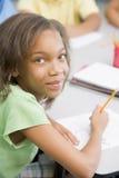 Pupila de la escuela primaria en el escritorio Imágenes de archivo libres de regalías