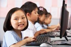 Pupila femenina que usa el teclado durante clase del ordenador Foto de archivo