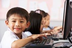 Pupila que usa el teclado durante clase del ordenador Fotografía de archivo