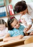 Pupilas de las ayudas del profesor para hacer la tarea Imagen de archivo