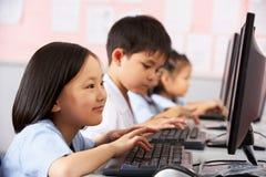 Pupilla femminile che per mezzo della tastiera durante il codice categoria del calcolatore fotografia stock libera da diritti