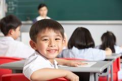 Pupilla maschio che funziona allo scrittorio a scuola cinese Immagine Stock