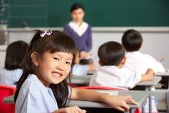 Pupille, die am Schreibtisch in der chinesischen Schule arbeitet Lizenzfreies Stockfoto