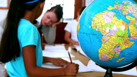 Pupils all siting around table working with focus on globe. In elementary school stock footage
