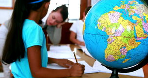 Pupils all siting around table working with focus on globe. In elementary school stock video footage