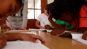 Pupils all working at the same desk in classroom. In elementary school stock video footage