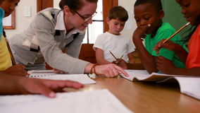 Pupils all working at the same desk in classroom. In elementary school stock footage