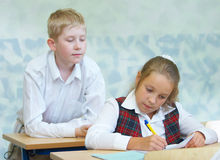 Pupils in a class. The boy tries to peep that the girl writes stock photography
