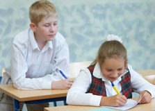 Pupils in a class. The boy tries to peep that the girl writes stock photos