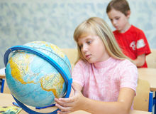 Pupils in a class. The schoolgirl considers the globe stock image