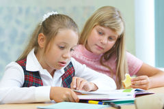 Pupils in a class. Girls doing homework together in a class stock image