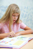Pupils in a class. The girl reading a book royalty free stock images