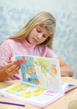 Pupils in a class. The girl reading a book stock photography