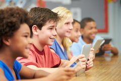 Pupils In Class Using Digital Tablet. Looking up and smiling Royalty Free Stock Photo