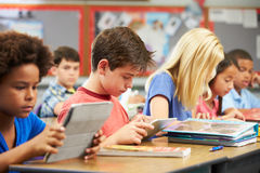Pupils In Class Using Digital Tablet. Students working at desk Royalty Free Stock Photo