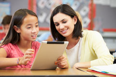 Pupils In Class Using Digital Tablet With Teacher Stock Image