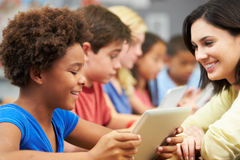Pupils In Class Using Digital Tablet With Teacher Royalty Free Stock Image