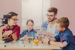 Pupils doing biochemistry research, stem education. Stem education. Pupils with teacher doing biochemistry research in chemistry class, using laboratory tubes royalty free stock photos