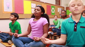 Pupils doing yoga in classroom