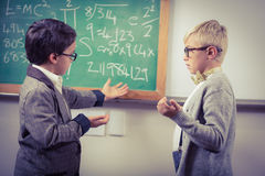 Pupils dressed up as teachers discussing in a classroom Royalty Free Stock Image