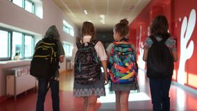 Pupils go through the school corridor. Two boys and two girls. Children carry backpacks. Back to school. Back view stock footage