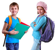 Pupils of grade school with backpack and books. Portrait of two smiling pupils of grade school with backpacks and books posing. Isolated over white background Royalty Free Stock Photos