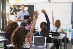 Pupils with hands raised in elementary school class Stock Photo