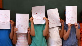 Pupils holding pages with faces stock video footage