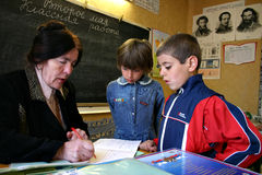 Pupils look like a school teacher checks homework Royalty Free Stock Photos