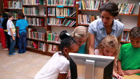 Pupils looking at the computer in library with their teacher. In elementary school stock video