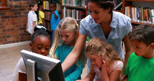 Pupils looking at the computer in library with their teacher. In elementary school stock video footage