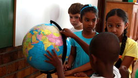 Pupils looking at the globe in classroom. In elementary school stock video