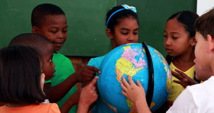 Pupils looking at the globe in classroom. In elementary school stock video footage