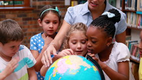 Pupils looking at the globe in library with their teacher. In elementary school stock video footage
