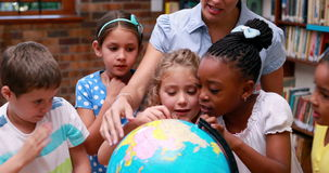 Pupils looking at the globe in library with their teacher. In elementary school stock footage