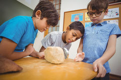 Pupils looking at rock with magnifying glass Royalty Free Stock Photos