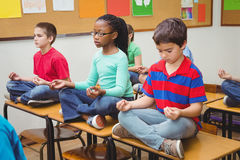 Pupils meditating on classroom desks Royalty Free Stock Images