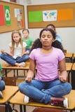 Pupils meditating on classroom desks Royalty Free Stock Photos