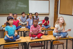 Pupils meditating in lotus position on desk in classroom Stock Photo