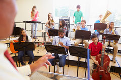 Pupils Playing Musical Instruments In School Orche. Stra In Classroom With Teacher Royalty Free Stock Photos