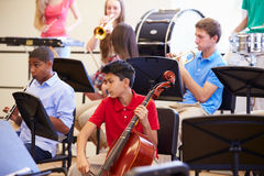 Pupils Playing Musical Instruments In School Orchestra. Happy Pupils Playing Different Musical Instruments In School Orchestra Royalty Free Stock Photography