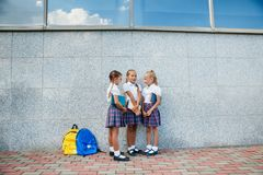 Portrait of school kids with backpack and books after school. Beginning of lessons. First day of fall. Pupils of primary school. Girls with backpacks and books Royalty Free Stock Photography