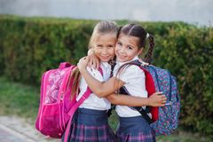 Portrait of school kids with backpack after school. Beginning of lessons. First day of fall. Pupils of primary school. Girls with backpacks near building Stock Photo