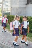 Portrait of school kids with backpack after school. Beginning of lessons. First day of fall. Pupils of primary school. Girls with backpacks near building Royalty Free Stock Images