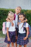 Portrait of school kids with backpack after school. Beginning of lessons. First day of fall. Pupils of primary school. Girls with backpacks near building Royalty Free Stock Photos