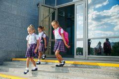Pupils of primary school. Girls with backpacks near building outdoors. Beginning of lessons. First day of fall. Portrait of school kids with backpack running Royalty Free Stock Images