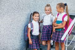 Portrait of school kids with backpack after school. Beginning of lessons. First day of fall. Pupils of primary school. Girls with backpacks near building Stock Photos