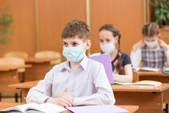 Pupils with protection mask against flu virus at lesson Royalty Free Stock Photography