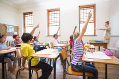 Pupils raising hand in classroom Stock Images