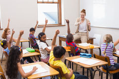 Pupils raising hand in classroom Royalty Free Stock Photos